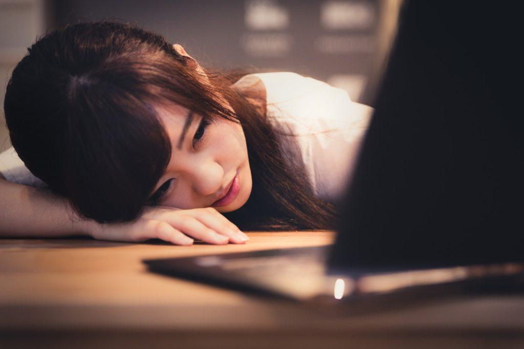 パソコンを見て疲れる女性